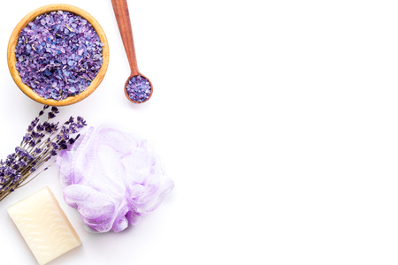 Spa set with lavender spa salt. Purple spa salt near dry lavender branches and washcloth on white background top view.