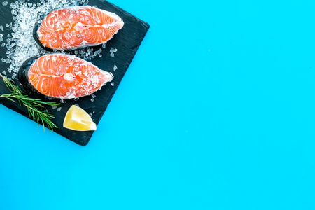 Raw salmon steak on black plate for cooking with lemon and rosemary on blue table background top view mockup