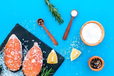 Raw salmon steak on black plate for cooking with spices and rosemary on blue table background top view