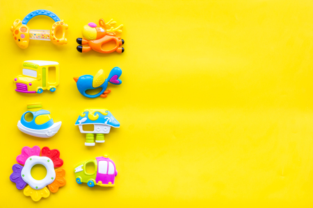 Handmade toys for newborn baby. Rattle. Yellow background top view mockup. Foto de archivo - 113424350