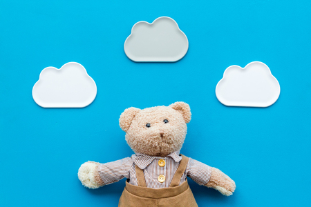 Toys for newborn baby set with teddy bear and clouds on blue desk background flat lay Stock Photo - 113424343