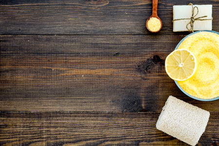 Lemon spa salt and spa accessories like soap, loofah, spa oil on dark wooden background top view.