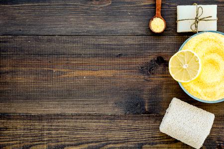 Sal de spa de limón y accesorios de spa como jabón, esponja vegetal, aceite de spa en la vista superior de fondo de madera oscura.