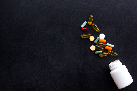 Close up of an open bottle of medicine and its lid. Several pills are lying on black desk. Pharmacology and medical supplies. Top view mock-up. Banco de Imagens