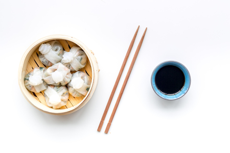 Chinese steamed dumplings Dim Sum in bamboo steamer with tea on white table background top view