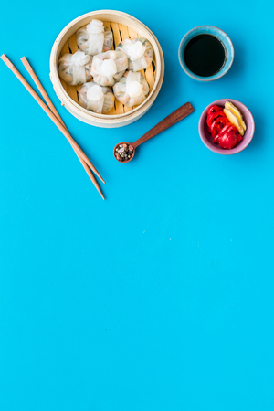 Chinese steamed dumplings Dim Sum with sweet paper and spices in bamboo steamer on blue table background top view mock up
