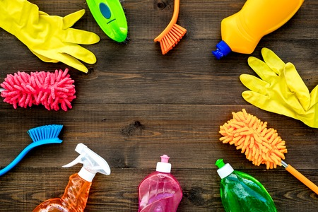 Housecleaning with detergents, soap, cleaners and brush in plastic bottles on wooden desk background top view mockup