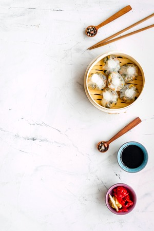 Dinner in Chinese restaurant with dim sum, sticks, spices and black tea on marble table background top view space for text