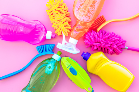 Housekeeping set. Detergents, soap, cleaners and brush for housecleaning on pink background top view mock-up.