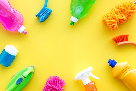 Housekeeping tool. Detergents, soap, cleaners and brush for housecleaner work on yellow background top view space for text. Stockfoto