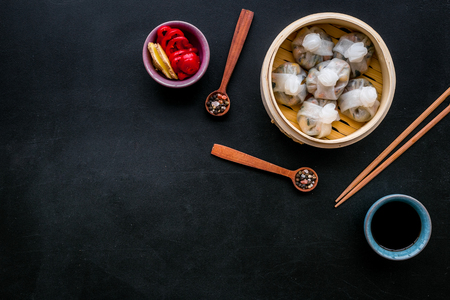Dinner in Chinese restaurant with dim sum, sticks and tea on black table background top view space for text