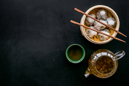 Dinner in Chinese restaurant with dim sum, sticks and herbal tea on black table background top view space for text Stock Photo