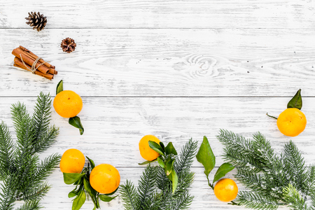 Branch of mandarins, fir tree and cinnamon for New Year and Christmas celebration on white wooden table background top view mockup
