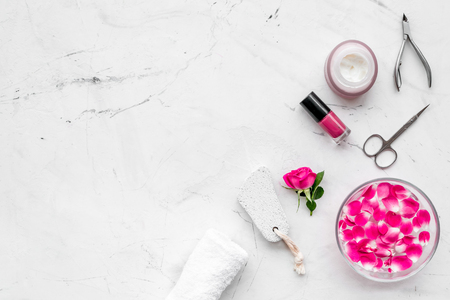 Tools for manicure with spa salt and rose on white stone
