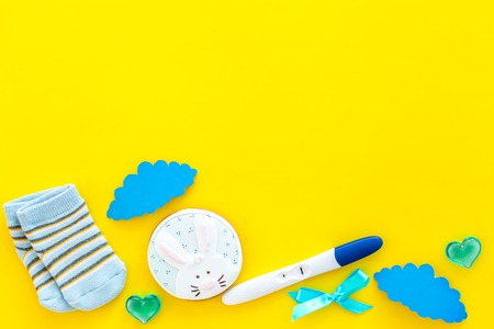 Waiting for a baby with positive pregnancy test, socks and hearts yellow