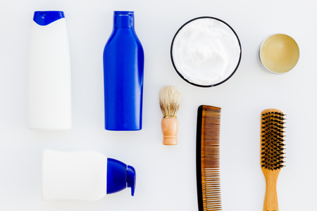 Instruments of male hairdresser with shampoo and comb in barbershop top view on white desk