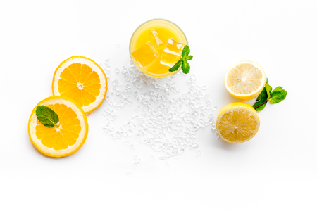Orange juice with ice cubes. Juice in glass near cut orange and lemon, crushed ice Banco de Imagens
