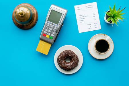 Electronic payments. Pay the bill by card concept. Bank card inserted in payment terminal near bill, service bell, coffee on blue Stock Photo