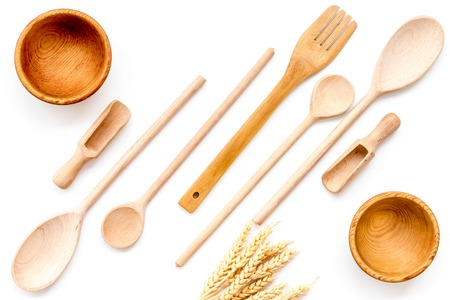 Fork, spoon, bowl in wooden-ware set on white table Imagens