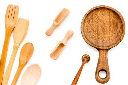 Holzgeschirrset mit Pfanne, Löffel und Gabel auf weiß Standard-Bild