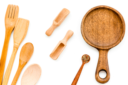 Wooden-ware set with pan, spoons and forks on white