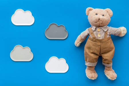 Toys for newborn baby set with teddy bear and clouds on blue desk Stockfoto