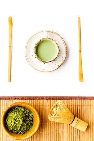 Coffee and cocktails with matcha concept. Matcha latte near bowl with matcha powder on white