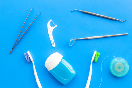 Daily oral hygiene for family. Toothbrush, dental floss and dentist instruments on blue table
