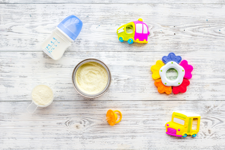 Toys for newborn baby set with plastic rattle and milk in bottle on white wooden