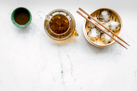 Dim sums with sticks and herbal tea in Chinese restaurant on marble table