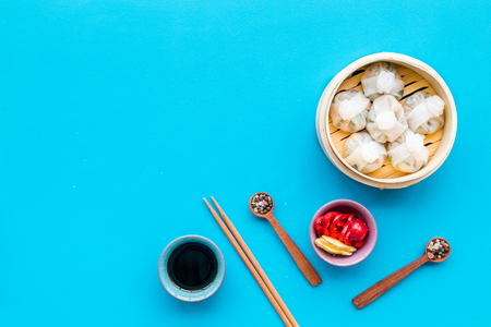 Chinese steamed dumplings Dim Sum with sweet paper and spices in bamboo steamer on blue table Stock Photo