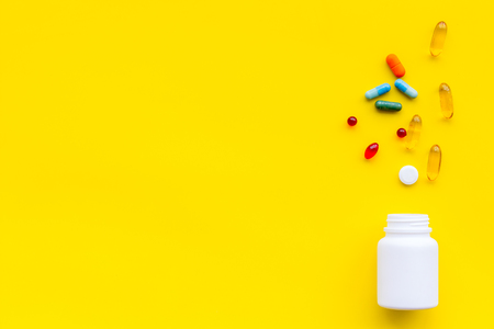 Close up of an open bottle of medicine and its lid. Several pills are lying on yellow desk.