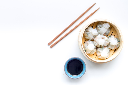 Chinese food set with dim sum, sticks and tea on white desk