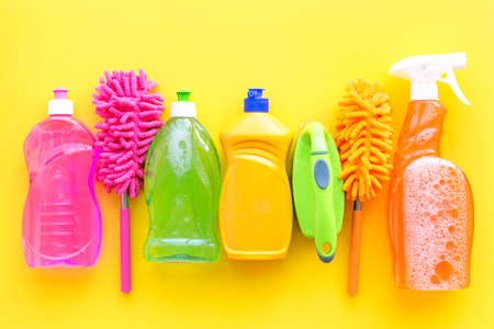 Housekeeping tool. Detergents, soap, cleaners and brush for house cleaner work on yellow