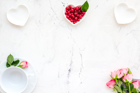 Elegant table setting with white plates, wine berry and floral decor on stone Stock fotó
