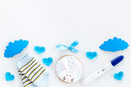 Pregnancy and preparation for childbirth. Babyshower. Pregnancy test near socks and hearts white background top view copy space