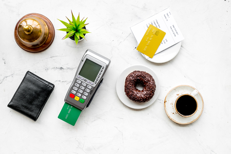 Electronic payments. Pay the bill by card concept. Bank card inserted in payment terminal near bill, service bell, coffee, donut on white stone background top view