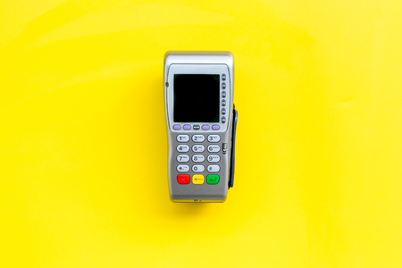 Payment terminal, compact POS terminal on yellow background top view copy space