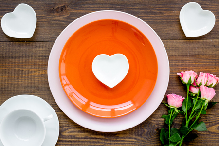 Elegant table setting with white plates and floral decor on wooden background top view Stockfoto