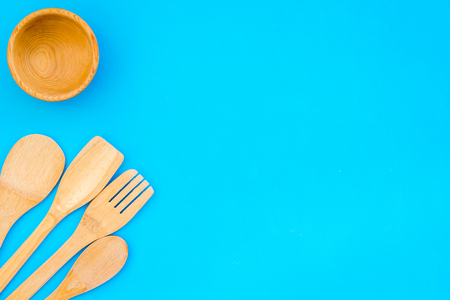 Fork, spoon, bowl in woodenware set on blue background top view space for text