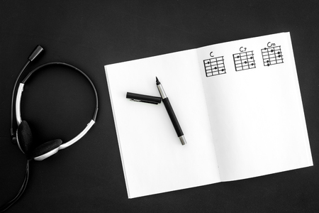 Desk of musician for songwriter work with headphones and notes black background top view mockup