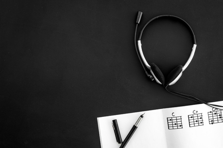 Desk of musician for songwriter work with headphones and notes black background top view mockup Stock Photo - 113741365