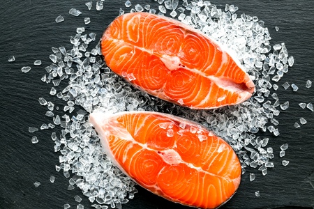 Raw salmon fish on black plates for cooking steaks. Restaurant kitchen background top view Stock Photo
