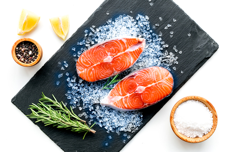 Cooking salmon steak from raw fish on black plate with spices, rosemary, lemon and salt on white restaurant kitchen table background top view Imagens
