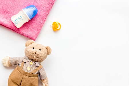 Craft toys for kids. Handmade teddy bear, dummy and baby bottle with milk. White background top view mock up