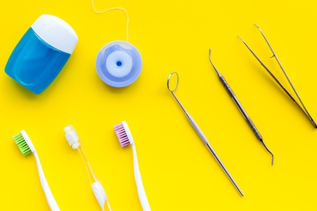 Tooth care with toothbrush, dental floss and dentist instruments. Set of cleaning products for teeth on yellow background top view