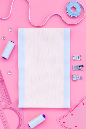 Tailor work place with thread, fabric. Sewing as hobby. Pink background top view space for text Stok Fotoğraf
