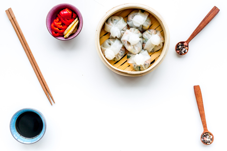 Chinese food set with dim sum, sticks and tea on white background top view copy space