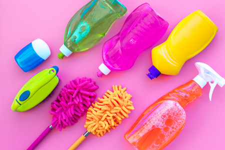 Housecleaning with detergents, soap, cleaners and brush in plastic bottles on pink background top view mockup