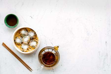 Dinner in Chinese restaurant with dim sum, sticks and herbal tea on marble background top view space for text